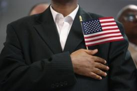 An immigrant recites the Pledge of Allegiance at a naturalization ceremony.